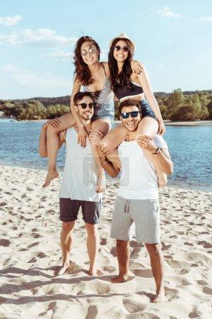 friends piggybacking on beach