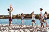 Friends playing volleyball on sandy beach
