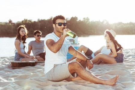 young man drinking beer on beach