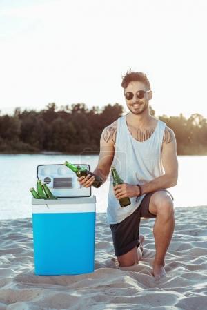 man taking beer from portable fridge
