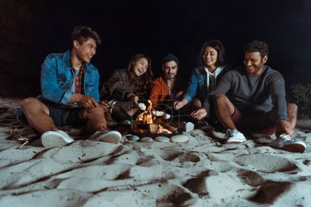 Photo for Young smiling multiethnic friends roasting marshmallows on bonfire at sandy beach - Royalty Free Image