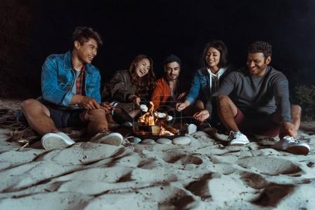 Multiethnic friends roasting marshmallows on bonfire