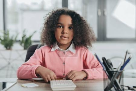 Photo for Little african american businesswoman with curly hair working with calculator in office - Royalty Free Image