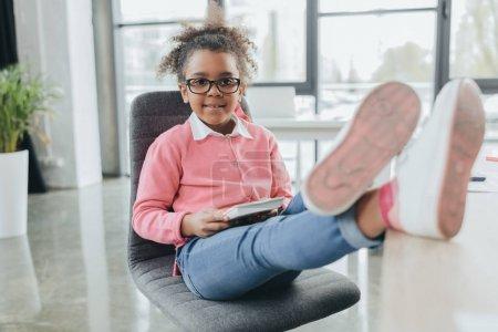 Photo pour Petite femme d'affaires afro-américaine souriante avec les jambes sur la table regardant la caméra dans le bureau - image libre de droit
