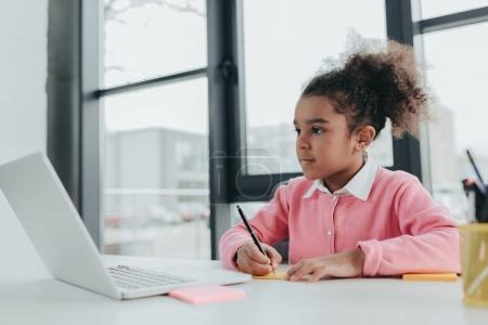 Photo for Adorable little african american girl using laptop while sitting at office table - Royalty Free Image