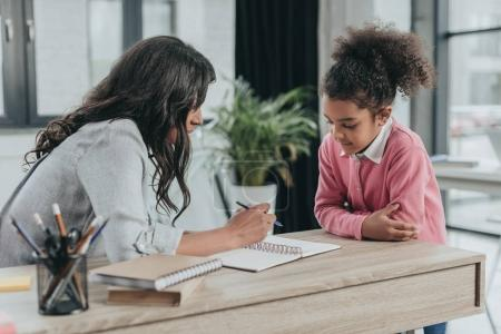 Photo pour Mère aider petite fille faire des devoirs dans le bureau d'affaires - image libre de droit