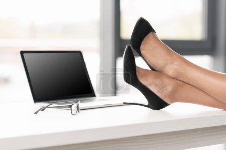 Photo pour Recadrée tir de femme d'affaires jambes croisées sur la table près de portable et lunettes - image libre de droit