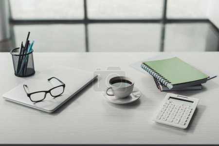 Photo for Laptop, eyeglasses and cup of coffee with office supplies on tabletop - Royalty Free Image