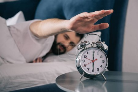 Photo for Bearded young man trying to turn off alarm clock while lying in bed at morning - Royalty Free Image