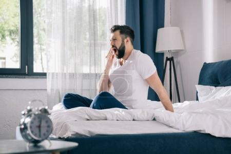 Photo for Bearded young man in pajamas yawning while sitting on bed in morning - Royalty Free Image