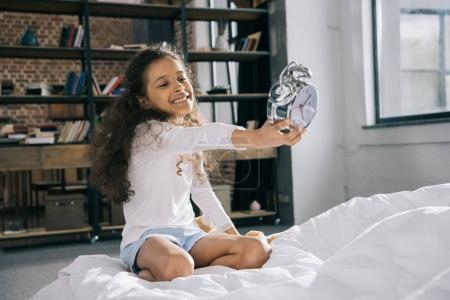 Girl holding alarm clock