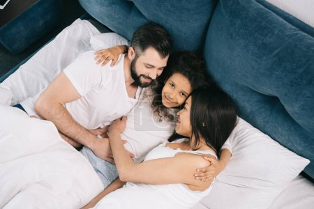 Photo for High angle view of happy multiethnic family hugging while lying together in bed - Royalty Free Image