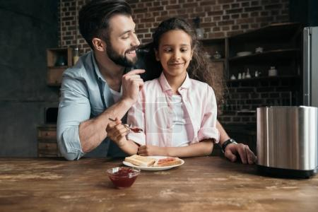 Photo for Girl having fun while preparing toasts with jam together with father for breakfast - Royalty Free Image