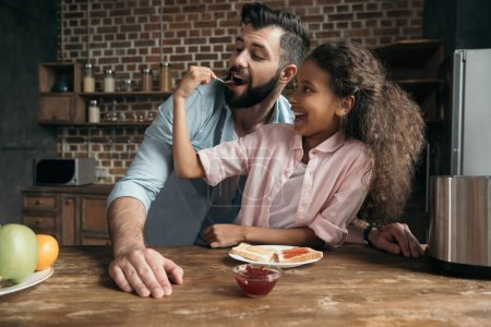 Photo for Happy girl feeding father with sweet jam from teaspoon - Royalty Free Image