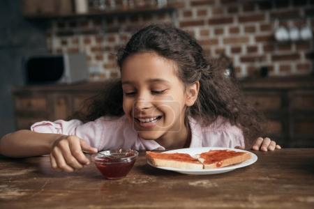 Girl looking at jam in bowl