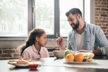father feeding girl with porridge