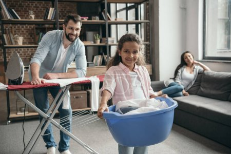 Multiethnic family ironing clothes