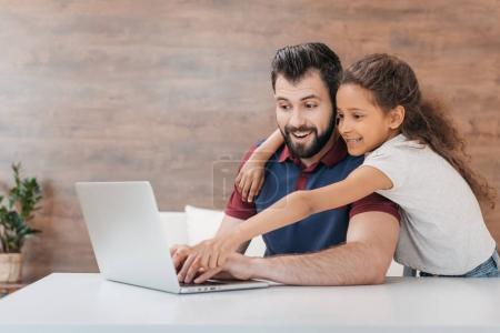 father and daughter with laptop