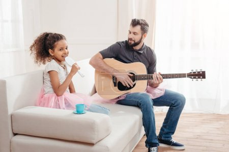Photo for Little african american girl singing while father playing guitar at home - Royalty Free Image
