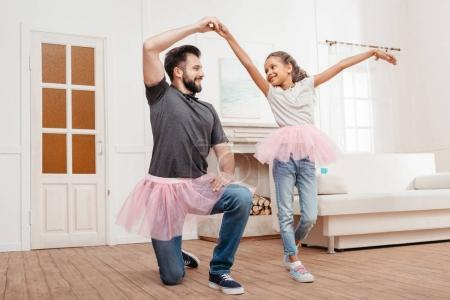 Photo for Multicultural father and daughter in pink tutu tulle skirts dancing at home - Royalty Free Image
