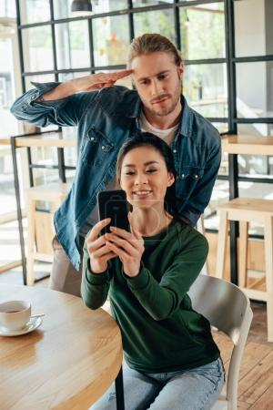 multiethnic couple taking selfie at cafe