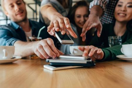 Foto de Jóvenes amigos recuperando sus teléfonos inteligentes tumbados en la pila sobre la mesa en la cafetería - Imagen libre de derechos