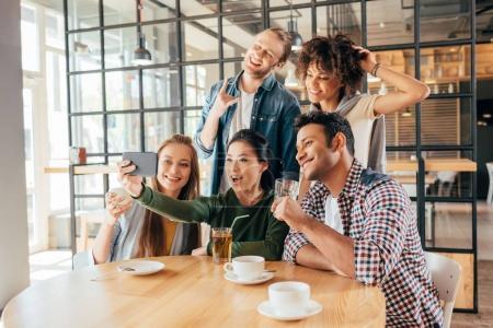 Photo pour Jeunes amis multiethniques heureux prenant selfie dans le café - image libre de droit