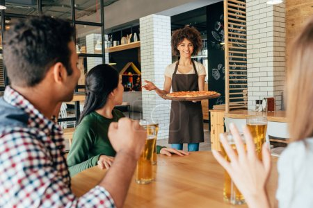 Photo for African american woman waitress bringing pizza for clients in cafe - Royalty Free Image