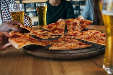 Friends with pizza and beer in cafe