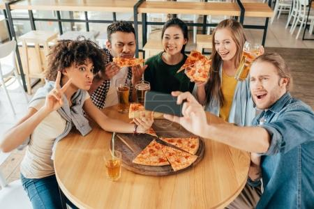 friends taking selfie with pizza at cafe
