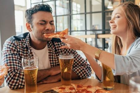 couple eating pizza at cafe
