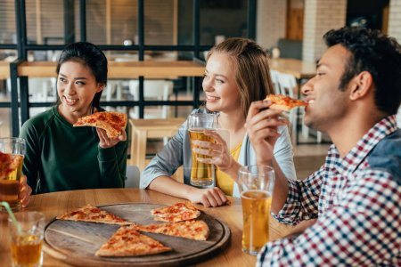Friends eating pizza with beer in cafe