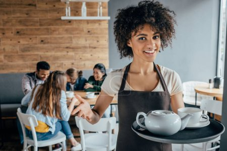 Photo for Smiling african american waitress holding tray with tea and customers sitting behind her in cafe - Royalty Free Image