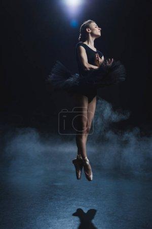 Photo pour Élégante ballerine dansant en pointes et tutu noir en studio avec fumée - image libre de droit