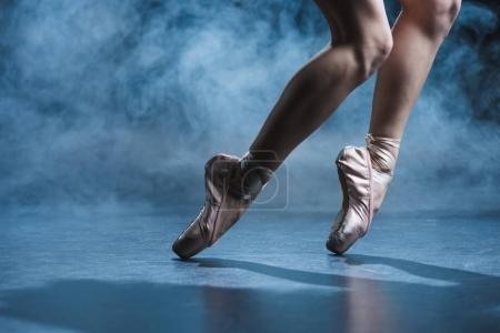 Photo for Cropped view of ballerina dancing in pointe shoes in dark studio with smoke - Royalty Free Image