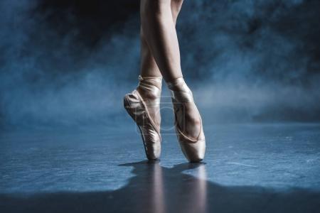 Photo pour Vue recadrée du danseur de ballet en pointe chaussures en studio sombre avec fumée - image libre de droit