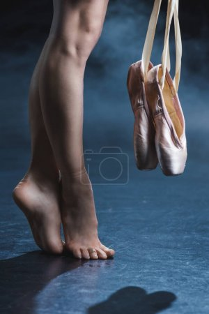 Barefoot ballerina holding pointe shoes