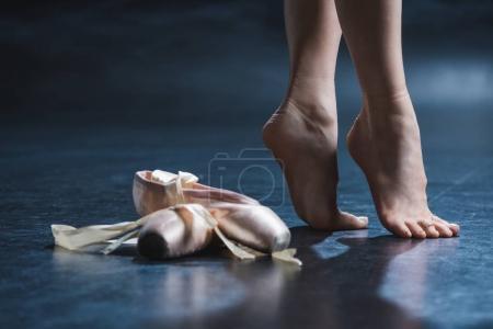Photo pour Vue recadrée élégante pieds nus ballerine et pointes chaussures en studio sombre - image libre de droit