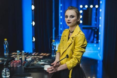 Photo pour Jolie ballerine en veste en cuir jaune appliquant le maquillage dans le dressing - image libre de droit