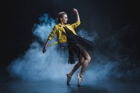 Photo for Attractive girl dancing in pointe shoes and black tutu and yellow leather jacket in studio with smoke - Royalty Free Image