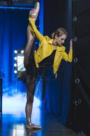 Photo pour Belle ballerine en tutu et veste en cuir jaune s'étirant dans le dressing - image libre de droit