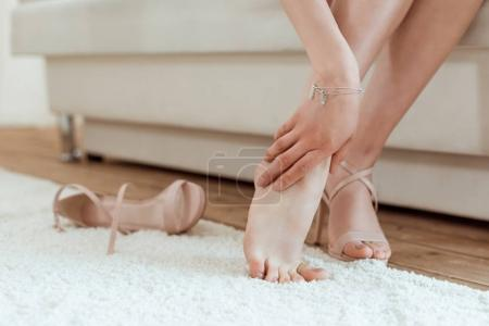 Photo for Cropped shot of tired woman taking shoes off and holding leg - Royalty Free Image