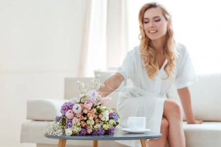 woman on sofa with wedding bouquet