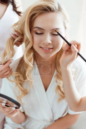 young woman getting makeup