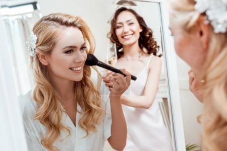 bride getting makeup before wedding