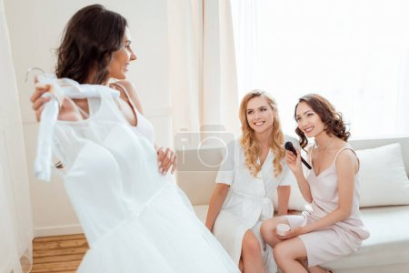 Photo for Young bride holding wedding dress bride while bridesmaids sitting on background - Royalty Free Image