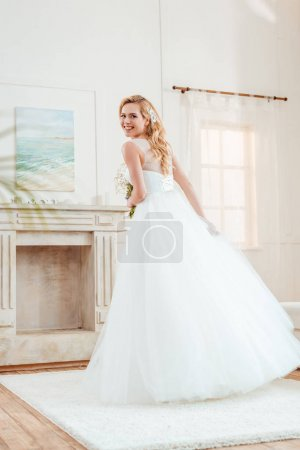 Photo for Beautiful young bride in wedding dress in living room - Royalty Free Image