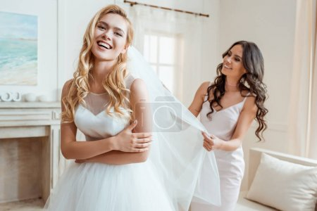 Photo pour Heureuse belle demoiselle d'honneur préparant mariée riante pour la cérémonie de mariage - image libre de droit