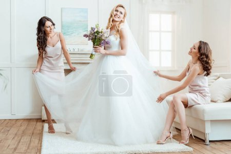 bride with bridesmaids preparing for ceremony