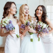 Beautiful laughing bride with bridesmaids holding ...